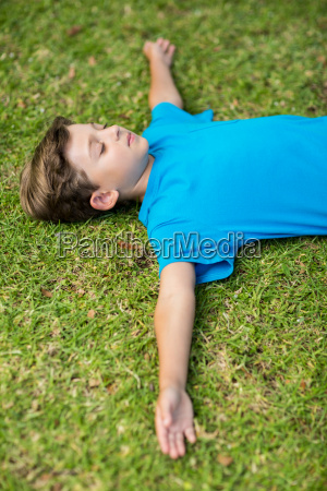 young boy sleeping in park