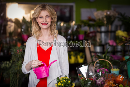 happy female florist holding a watering
