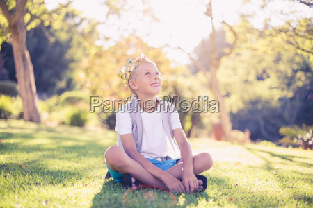 young boy sitting in park