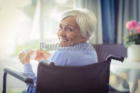 happy senior woman on wheelchair holding