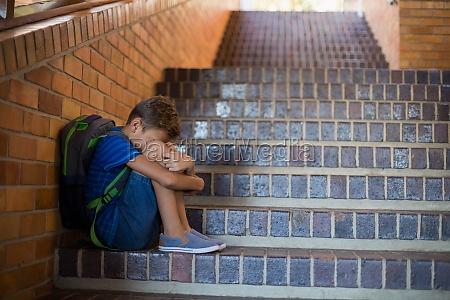 trauriger schuljunge sitzt allein auf treppe