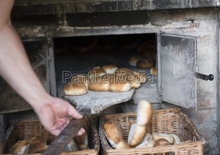 a man sliding bread rolls out