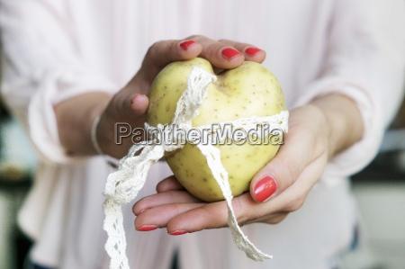 a womans hands holding a heart