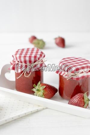 zwei glaeser erdbeermarmelade auf einem tablett