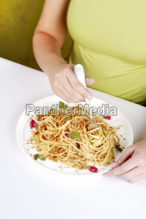 a woman eating spaghetti with anchovies