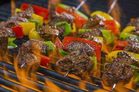 rinderspiesse mit paprika auf einem flammenden