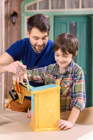 happy father and son painting wooden