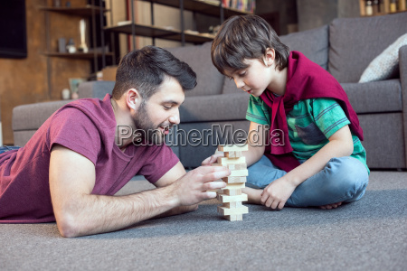 smiling father and concentrated son playing