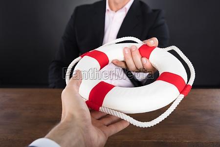 businessman passing a lifebuoy to a