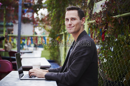 a young man sitting outdoors at
