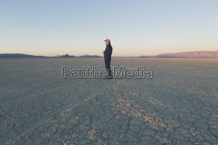 man standing in vast desert playa