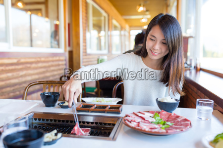 woman eating barbecue beef in japanese