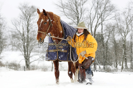 woman walking with horse in snow