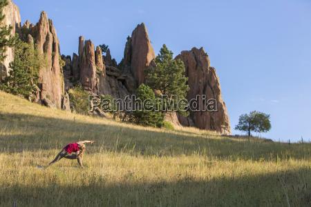 woman practicing yoga on grassyland outside