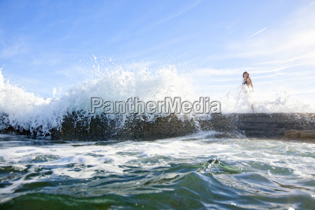 woman walking on rock with water