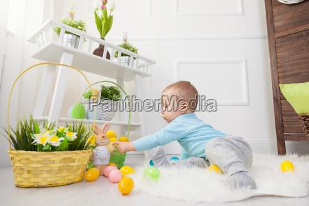 ostereiersuche entzueckendes kind mit ostereiern spielen