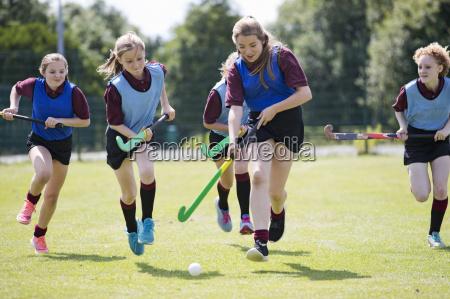middle schoolgirls playing field hockey on