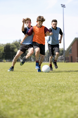 middle schoolboys running playing soccer on