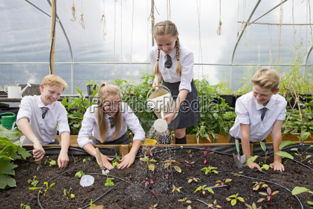 middle school students with watering can