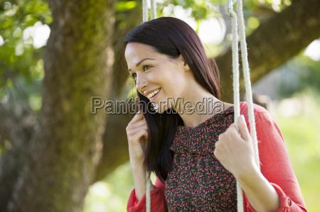 happy brunette woman swinging on tree