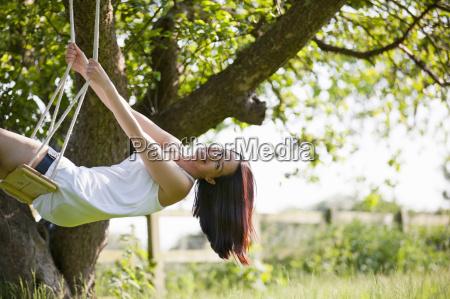 portrait happy woman swinging on tree