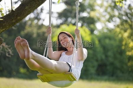 happy barefoot woman swinging on tree