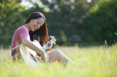 happy woman playing guitar in sunny