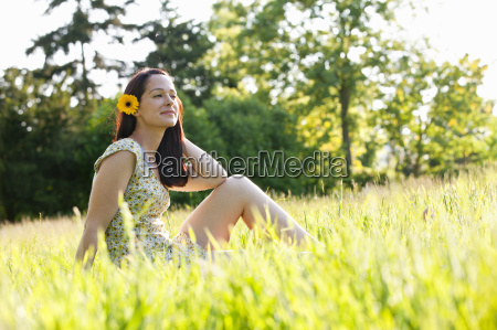 carefree brunette woman with flower in