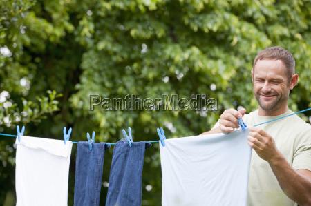 man hanging laundry clothing on clothesline