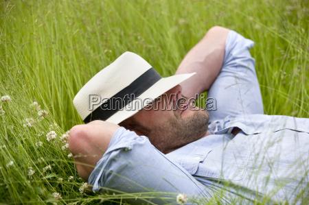 serene man wearing fedora sleeping in