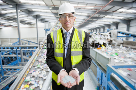 businessman in recycling plant holding plastic