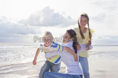 mother hugging children on beach vacation