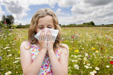 girl suffering from hayfever sneezing in