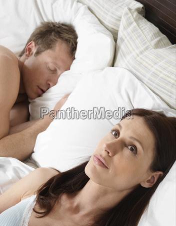 woman lying awake in bed while