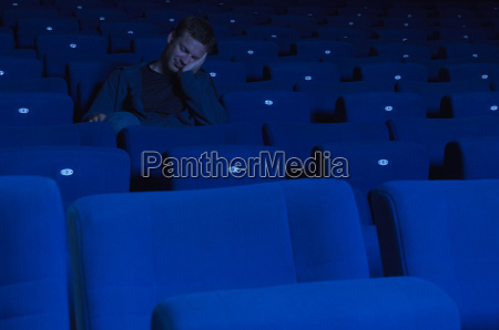 man sleeping in movie theatre