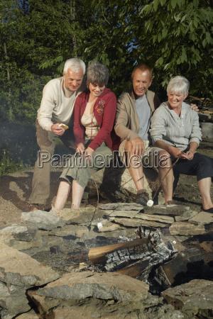 couples roasting marshmallows around fire