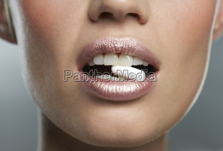 woman with pill in mouth