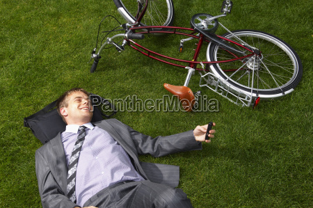 businessman lying on grass