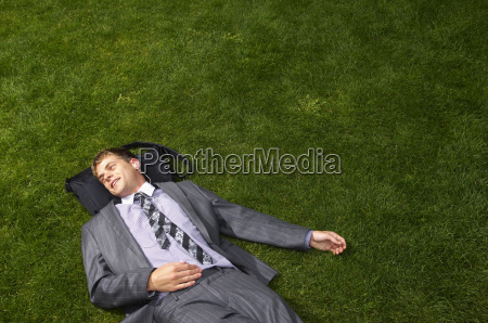businessman lying on grass listening to