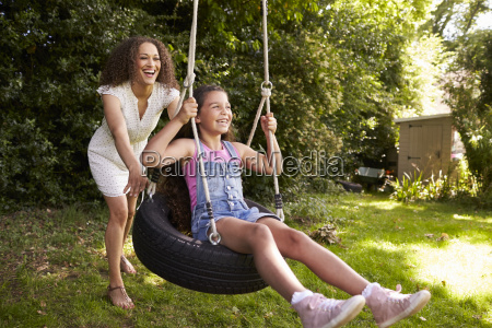 mother pushing daughter on tire swing