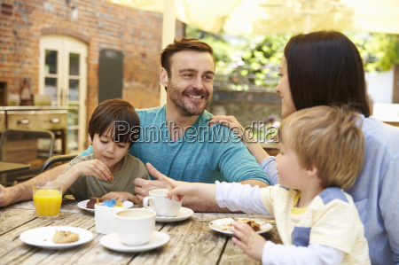family sitting at outdoor cafe table