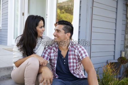 affectionate couple sitting on steps outside