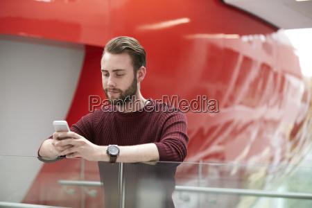 baertiger maennlicher schueler mit smartphone im