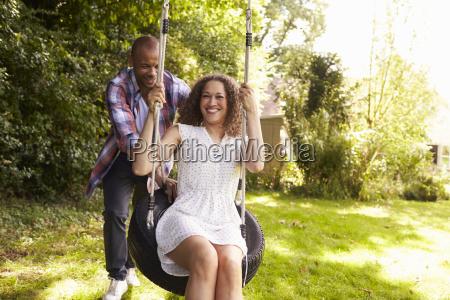 man pushing woman on tire swing