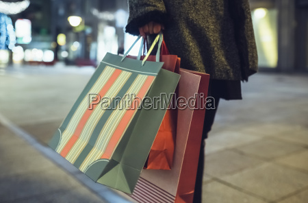 woman with shopping bags on pavement