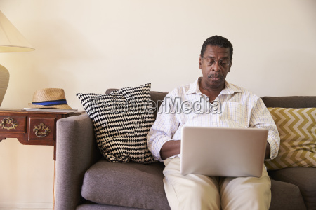 senior man sitting on sofa at