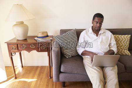 senior man sitting on sofa at