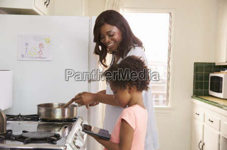 mother and daughter at home preparing