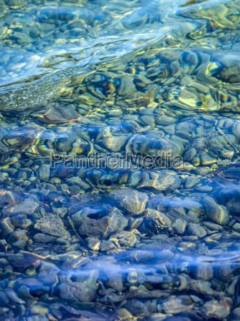 kieselsteine unter klarem wasser eines sees