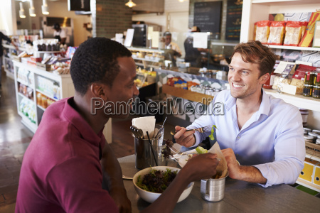 two men enjoying lunch in delicatessen